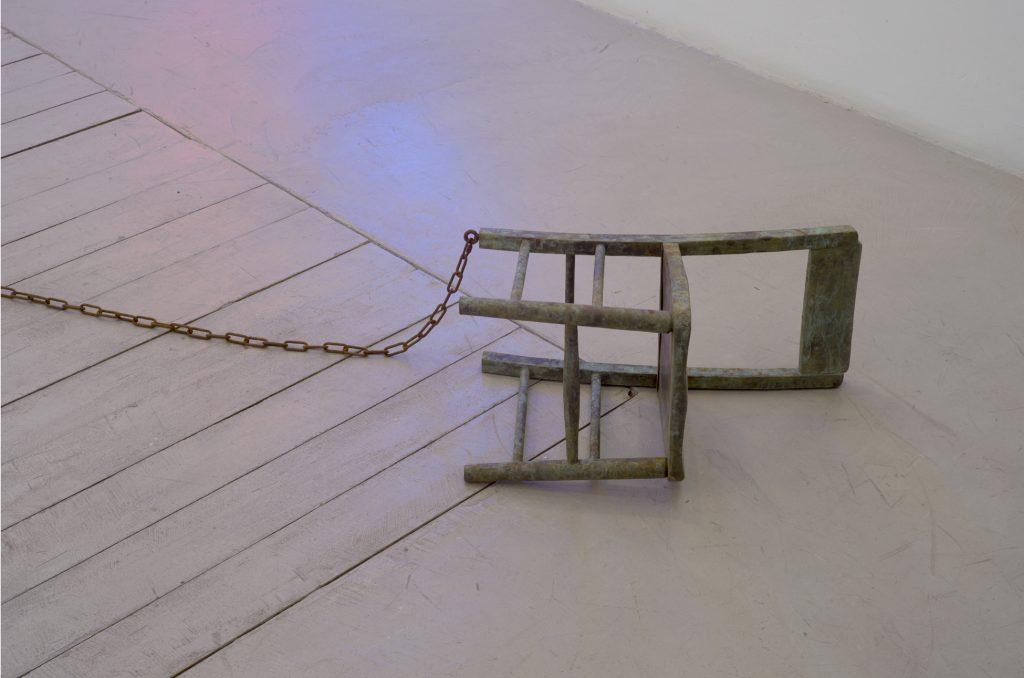 John Isaacs, Cast from light and dark your shadow is no different from mine, 2013, chained child chair of patinated bronze, steel, variable dimensions, ed. of 4 + 2 AP. Courtesy the artist and Aeroplastics contemporary, Brussels.