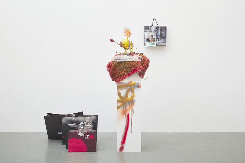 Isa Genzken, Untitled, 2016 Pedestal, rug, spray paint, mixed media (globe, feather, plastic toy figures, artificial rose, carpet, tape, spray paint, wooden pedestal, 5 paper bags with tape, plastic tube, plastic card, photograph) sculpture, 190 x 70 x 60 cm / 74.8 x 27.5 x 23.6 inches bags 50 x 120 x 110 cm / 19.6 x 47.2 x 43.3 in.  Courtesy the artist, Hauser & Wirth and Galerie Buchholz Cologne / Berlin / New York © Artists Rights Society (ARS) New York / VG Bild-Kunst, Bonn. Photo: Nick Ash