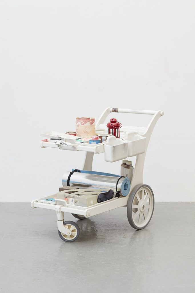 Isa Genzken, Untitled, 2016 Mixed media, trolley, tapes, printed adhesive foil, pens, metal lamp, plastic can, film container, air pump, cord, cable, mirror foil, stickers, plastic magazine stand, thermal mat. 83 x 105 x 61 cm / 32 5/8 x 41 3/8 x 24 in. Courtesy the artist, Hauser & Wirth and Galerie Buchholz Cologne / Berlin / New York © Artists Rights Society (ARS) New York / VG Bild-Kunst, Bonn. Photo: Nick Ash
