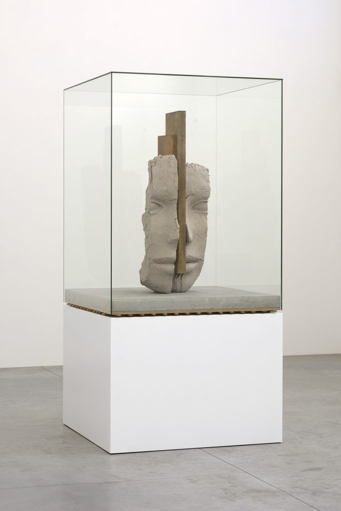 Mark Manders 'Dry Clay Head on Concrete Floor', 2016. 252,5 x 127 x 127 cm, painted bronze, painted wood, offsetprint on paper, concrete, iron, glass, (edition of 3 + 1 AP). Courtesy the artist and Zeno X Gallery. Photo: Peter Cox