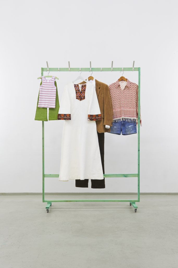 Silke Schatz 'Reigen', 2013 green etched roof batten, coat hangers, clothes, hooks, rolls. 212,5 x 147 x 52 cm. Courtesy Meyer Riegger.