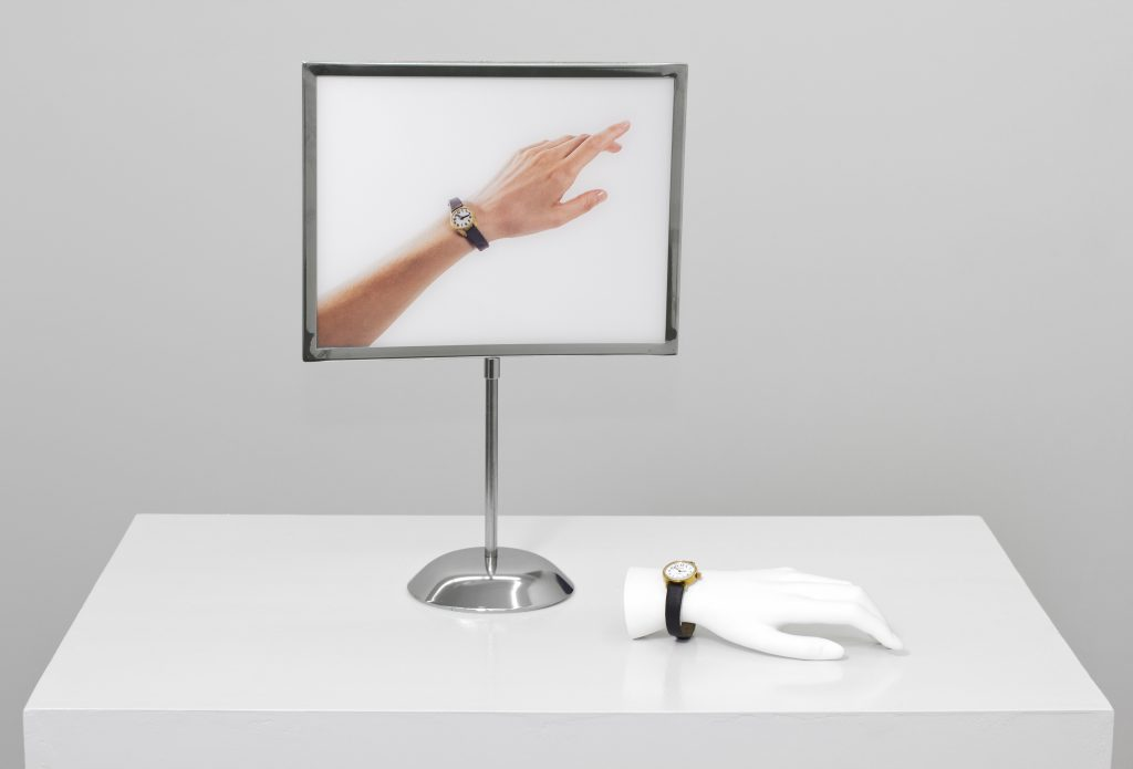 Jamie Isenstein 'Hand Watch Watch Hand' (Ed. 1/2), 2016 C-print mounted on plexi, display stand, mannequin hand, plaster, wound-up watch, mannequin hand: 4 x 20 x 7,5 cm, print: 40,5 x 28 x 10 cm. Courtesy Meyer Riegger.